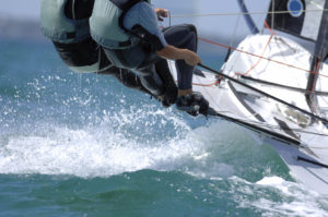 Sailors splash through the waves during a regatta.